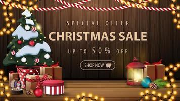 oferta especial, liquidação de natal, até 50 de desconto, lindo banner de desconto com decoração de natal, guirlandas, lanterna vintage e árvore de natal em uma panela com presentes perto da parede de madeira