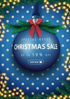oferta especial, liquidação de natal, desconto de até 50, banner azul de desconto vertical com uma grande bola de natal azul com oferta, guirlanda, textura de bolinhas, árvore de natal e laço vermelho