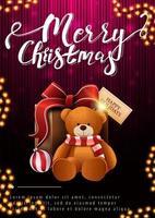 Feliz Natal, postal vertical com presente e ursinho de pelúcia em fundo escuro e rosa