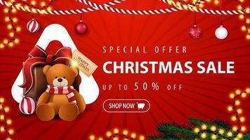 oferta especial, liquidação de natal, desconto de até 50, banner vermelho de desconto com guirlandas, galhos de árvores de natal, bolas, triângulo branco grande e presente com ursinho de pelúcia