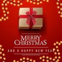 Feliz Natal e Feliz Ano Novo, postal quadrado vermelho com guirlanda e presente com laço, vista de cima