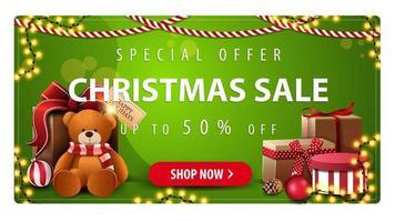 oferta especial, liquidação de natal, até 50 de desconto, banner horizontal verde com botão, guirlandas e presentes com ursinho de pelúcia