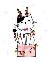 gatinho branco usando chifres de rena em uma caixa de presente