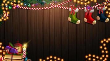 modelo de Natal de vetor com guirlanda, ramo, livros, vela no fundo de madeira