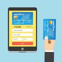 mão humana segurando cartão de crédito com tablet vetor