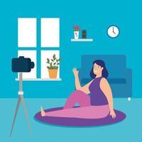 mulher praticando gravando uma aula de ioga na sala de estar vetor