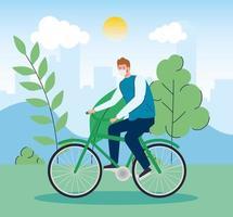 homem andando de bicicleta ao ar livre com máscara facial