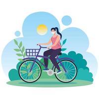 mulher andando de bicicleta ao ar livre com uma máscara facial