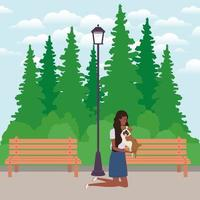 jovem mulher afro levantando um cachorro fofo no parque vetor