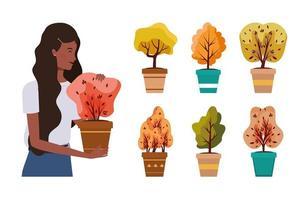 mulher afro com plantas de outono em vasos de cerâmica vetor