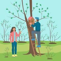 um jovem e uma mulher pendurando uma casa de passarinho em uma árvore