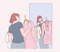 uma mulher está segurando um vestido e se olhando no espelho. vetor