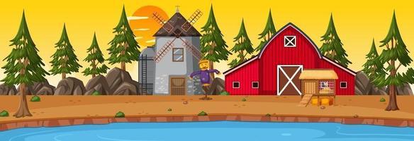 cena horizontal de terras agrícolas com celeiro e moinho de vento no pôr do sol