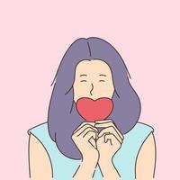 história de amor ou conceito de dia dos namorados. jovem sorridente cobre a boca com um coração de papel vermelho. vetor