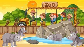 zoológico na hora do pôr do sol com muitas crianças assistindo o grupo de rinocerontes vetor