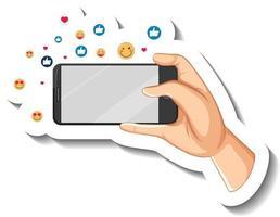 um modelo de adesivo de mão segurando um telefone inteligente com o ícone de emoji social vetor