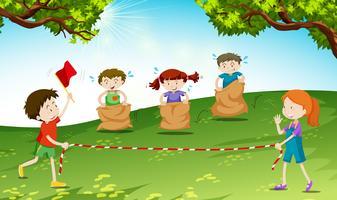As crianças brincam pulando saco no parque