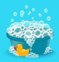 bacia azul com espuma de sabão e pato de borracha amarelo. vetor