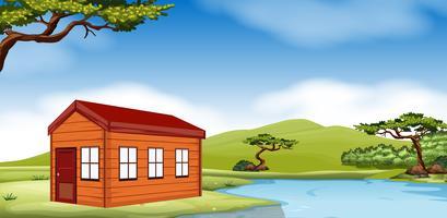 Casa de madeira à beira da lagoa vetor