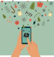 mão humana segurando um telefone celular com elementos de natal voando para fora da tela vetor