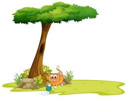 Um gato laranja brincando debaixo da árvore vetor