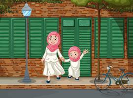 Meninas muçulmanas na calçada vetor