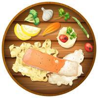 Molho de creme de salmão e macarrão na tábua de madeira vetor