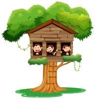 macaco jogando na casa da árvore vetor