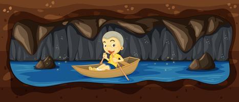 Um garoto andando de barco na caverna do rio