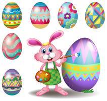 Um coelho pintando os ovos vetor
