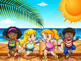 Quatro crianças felizes à beira-mar vetor