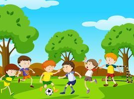 Meninos jogando futebol no parque vetor