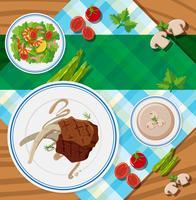 Cena de mesa com bifes e salada