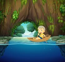 Garotinho no barco a remos de madeira