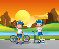 Duas crianças com suas bicicletas em pé na estrada perto do rio vetor
