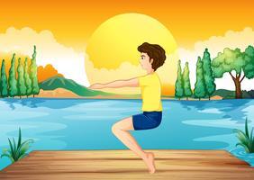 Um menino exercitando perto do rio profundo