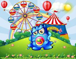Um monstro de bebê no topo da colina com um carnaval vetor