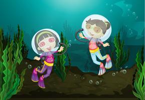 Meninas felizes que mergulham debaixo d'água