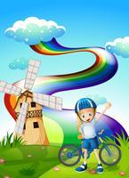 Um jovem motociclista no topo da colina com um moinho de vento e um arco-íris vetor