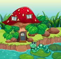 Um verme perto da casa de cogumelo vermelho vetor
