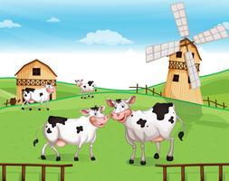 Vacas no topo da colina com um moinho de vento vetor