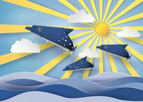 Origami fez golfinho e barco à vela Flutuam no mar com Origami feito golfinho e barco à vela Flutuam no mar com raio de sol