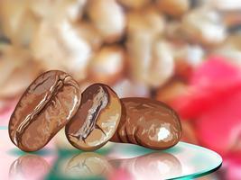 Semente de café na mesa de vidro com fundo de borrão de café