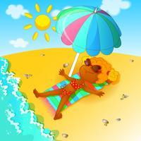 Uma menina em um maiô sunbathes sobre a praia sob um guarda-chuva de praia.