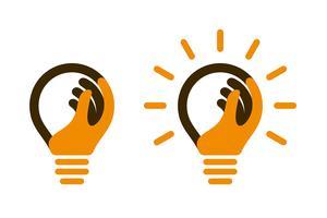Ícones de lâmpada com mão humana e feixes de luz vetor