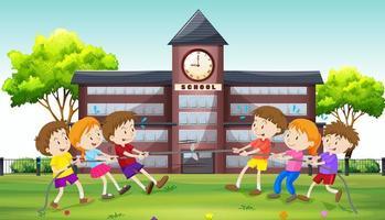 Crianças brincando de cabo de guerra na escola vetor
