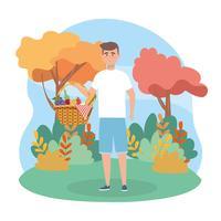 Homem com cesta de piquenique no parque vetor
