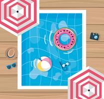 Vista aérea da piscina com guarda-chuvas e brinquedos de piscina