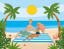 Casal deitado na toalha na praia