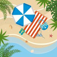 Vista aérea de guarda-chuva, toalha, sandálias e roupa de banho na praia